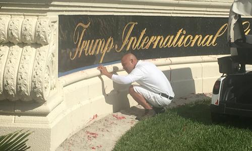 Nhân viên lau mực đỏ dính trên đá trước câu lạc bộ gold quốc tế Trump. Ảnh: Twitter.