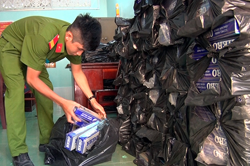 Mở các khoan chứa tự chế trên xe tải, cảnh sát phát hiện 18.000 gói thuốc lá lậu. Ảnh: Lan Vy