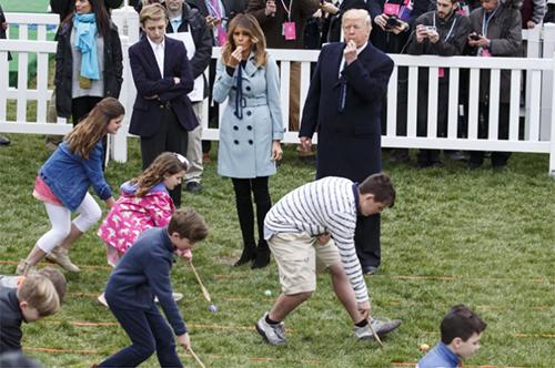 Vợ chồng Trump thổi còi để bắt đầu cuộc đua lăn trứng dành cho trẻ em. Ảnh: Bloomberg