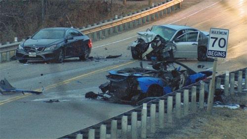 Siêu xe Lamborghini màu xanh nát bấy sau tai nạn. Bên đường là biển giới hạn tốc độ.