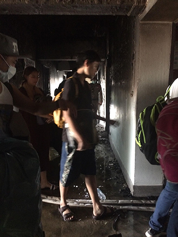 Người dân được phép trở lại chung cư cháy thu thập đồ đạc. Ảnh: Nguyễn Hiền