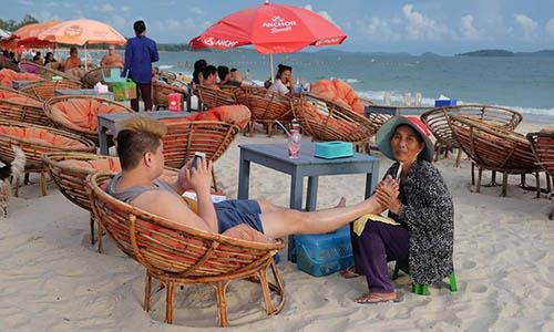Khách du lịch Trung Quốc ngồi mát-xa chân trên bãi biển ởSihanoukville,phía nam Campuchia. Ảnh: Nation.