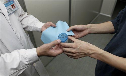 Một người đàn ông trao mẫu tinh trùng của mình cho các bộ bệnh viện tinh trùng Hà Nam ở thành phố Trịnh Châu, tỉnh Hà Nam, năm 2015. Ảnh: CFP.