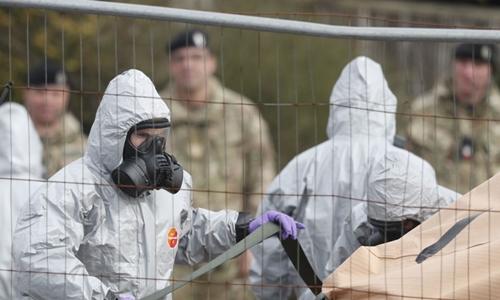 Lính Anh ngày 14/3mặc đồ bảo hộ tiếp xúc với một phương tiện có liên quan tới vụ đầu độc cựu điệp viên. Ảnh: AFP.