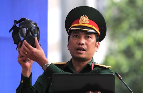 Thiếu tá Đào Xuân Thành hướng dẫn người dân cách sử dụng mặt nạ phòng độc. Ảnh: Gia Chính