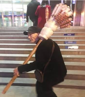 Một cụ ông bán kẹo hồ lô trên phố. Ảnh: SCMP.