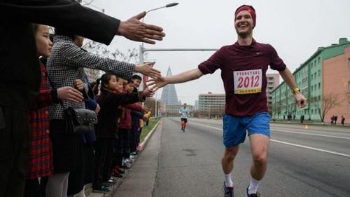 Người dân đứng ven đường, chìa tay cổ vũ cho các vận động viên đến từ phương Tây. Ảnh: AFP.