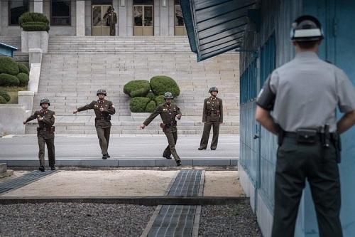 Một binh sĩ thuộc Bộ Chỉ huy Liên Hợp Quốc quan sát binh sĩ Triều Tiên đi về phía đường phân định ở Panmunjom hồi tháng 10/2017. Ảnh: AFP.