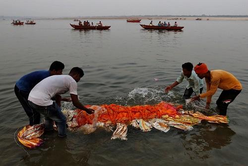 Người theo đạo Hindu nhúng thi thể người chết vào dòng nước thánh sông Hằng trước khi đi hỏa táng. Ảnh: Reuters