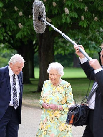 Nữ hoàng Elizabeth II quay phim tài liệucùng người dẫn chương trình David Attenborough ở vườn củacung điệnBuckingham hè năm ngoái. Ảnh: ITV