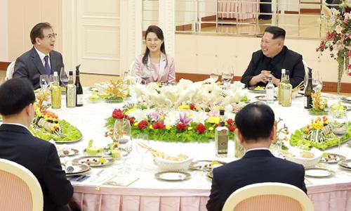 Nhà lãnh đạoKim Jong-un và phu nhân Ri Sol-ju(áo hồng) đãi tiệc tốicác đặc phái viên Hàn Quốc. Ảnh:The Blue House