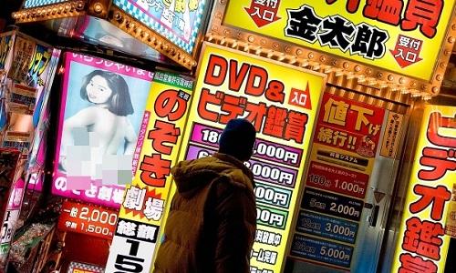 Một người đàn ông ngước nhìn bảng giá xem phim người lớn tại một cơ sở kinh doanh ở Tokyo. Ảnh: Economist.