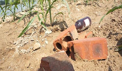 Gạch đá và bom xăng tự chế đựng trong các vỏ chai vứt la liệt ven bờ sông Chu ở xã Thiệu Đô. Ảnh: Lê Hoàng.