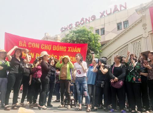 Nhiều tiểu thương căng băng rôn phản đối xây chợ sáng 9/4. Ảnh: Giang Huy.