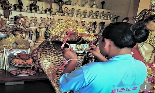 Nhiều người còn nhét cả tiền giấy vào miệng tượng rắn để chắc chắn mong ước của mình thành hiện thực. Ảnh: SCMP.