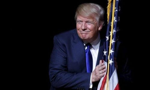 Trump ôm quốc kỳ Mỹ khi tham dự buổi gặp gỡ cử tri tại Derry, New Hampshire năm 2017. Ảnh: Reuters.
