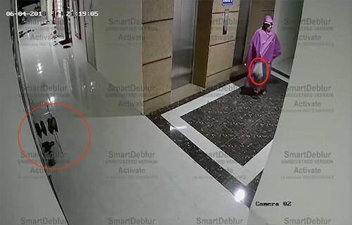 Thời điểm rạng sáng 6/4, Công (mặc áo mưa, thủ bọc chất bẩn ở tay) chuẩn bị ném vào cửa phòng chung cư (khoảnh đỏ). Ảnh: Cắt tử video an ninh.