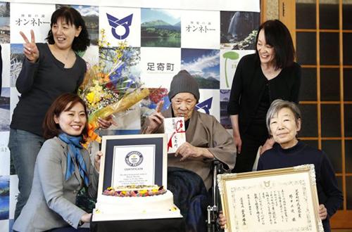Đại diện Tổ chứcKỷ lục Guinness Thế giới (áo màu ghi) và người thân chung vui với ông Nonaka tại buổi lễ. Ảnh: Reuters