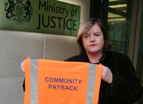 Chiếc áo phản quang màu cam với dòng chữ community payback (tạm hiểu là gửi trả cộng đồng) dành cho người phải lao động công ích.