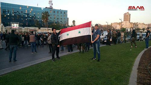 Người dân cầm quốc kỳ Syria ủng hộ chính quyền ở quảng trườngUmayyin, Damascus. Ảnh: SANA