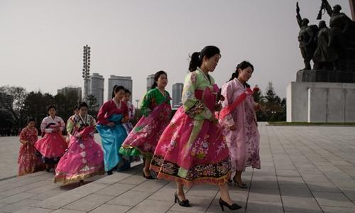 Các cô gái đến đặt hoa tại tượng Kim Nhật Thành ngày 15/4. Ảnh: AFP.