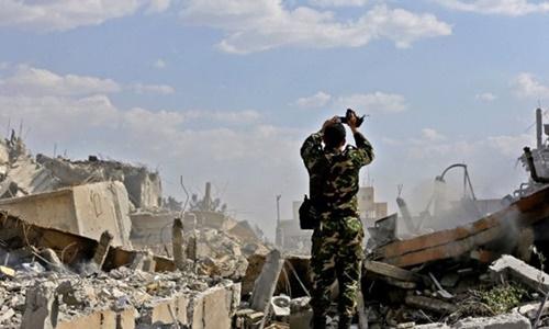 Binh sĩ Syria xem xét đống đổ nát của một trung tâm nghiên cứu phía bắc thủ đô Damascus. Ảnh: AFP.
