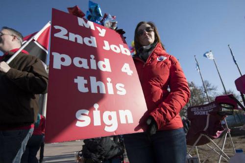 Một giáo viên ở Oklahoma với thông điệpNghề thứ hai của tôi trả tiền cho tấm biển này trong cuộc biểu tình ngày 4/4. Ảnh: Getty Images