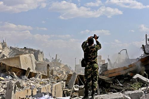 Một binh sĩ Syria tạiđống đổ nát ở Trung tâm Nghiên cứu Khoa học tại quậnBarzeh, Damascus, hôm 14/4, sau cuộc không kích của Mỹ. Ảnh: AFP