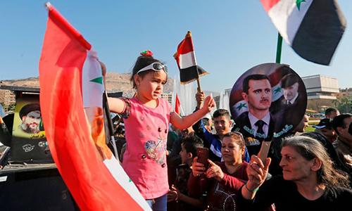 Người dânvẫy cờ và ảnh Tổng thốngBashar al-Assad ở quảng trườngUmayyad, Damascus hôm 14/4, để ủng hộ chính phủ và phản đối liên minh do Mỹ dẫn đầu. Ảnh: AFP