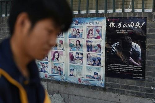 Một thanh niên đi ngang qua áp phích tuyên truyền phim hoạt hình chống mỹ nam kế của gián điệp nước ngoài ở Bắc Kinh hồi tháng 5/2017. Ảnh: AFP.