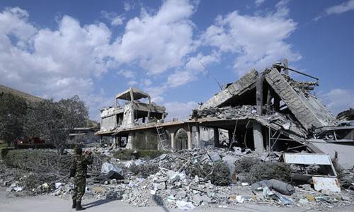 Một binh sĩ Syria quay lại cảnh đổ nát ở trung tâm nghiên cứu khoa học gần thủ đô Damascus sau vụ không kích của liên quân Mỹ, Anh và Pháp sáng ngày 14/4. Ảnh: AP.