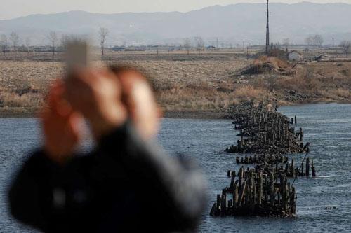 Một người đàn ông chụp ảnh với phần còn sót lại của một cây cầu bị tàn phá trong Chiến tranh Triều Tiên, ở phía bắc thành phố Đan Đông, tỉnh Liêu Ninh, Trung Quốc. Ảnh: Reuters.
