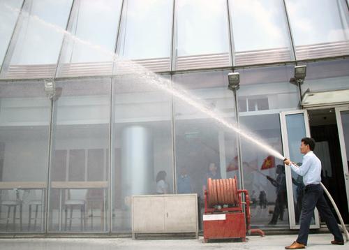 Nhân viên toà nhà Bitexco phun thử nước chữa cháy tại tầng 52. Ảnh: Duy Trần.