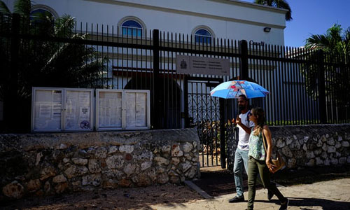 Hai người đi bộ ngang qua đại sứ quán Canada đóng tại thủ đô Havana, Cuba. Ảnh: Reuters.