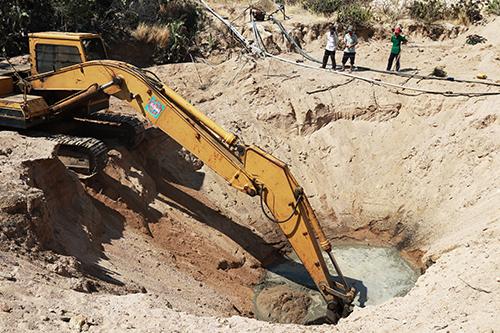 Nhiều người ở huyện Nhơn Hải tìm đủ cách tìm nguồn nước để tưới tiêu, họ thuê máy múc đào hố để có nước. Ảnh: Xuân Ngọc