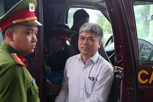 Ông Nguyễn Xuân Sơn rời xe cảnh sát vào phiên phúc thẩm. Ảnh: Phạm Dự