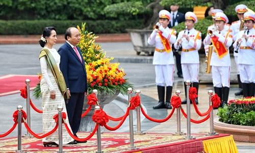 Thủ tướng Nguyễn Xuân Phúc và Cố vấn Nhà nước Myanmar Aung San Suu Kyi trên bục danh dự, quân nhạc cử quốc thiều hai nước. Ảnh: Giang Huy.