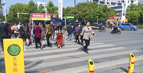 Người đi bộ qua đường ở một điểm lắp đặthệ thống cọc phun nước tự động và nhận dạngngười vượt đèn đỏ tạithành phố Đại Dã, tỉnh Hồ Bắc. Ảnh:Weibo