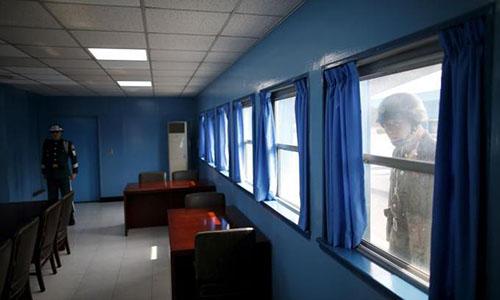 Một người lính Triều Tiên ghé mắt nhìn vào một phòng họp trong số ba phòng họp ở Khu vực An ninh Chungdo Liên Hợp Quốc kiểm soát, trong khi đó một lính Hàn Quốc đứng gác bên trong. Ảnh: Reuters.
