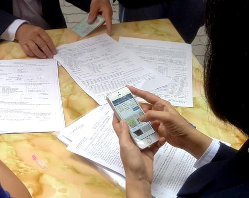Các nhân viên của mobifone sử dụng điện thoại chụp chứng minh thư, thẻ căn cước và chân dung chủ thuê bao, sau đó mới nhập vào hệ thống. Việc này khiến nhiều khách hàng lo ngại thông tin cá nhân cảu họsẽ rất dễ bị lộ. Ảnh: Giang Chinh