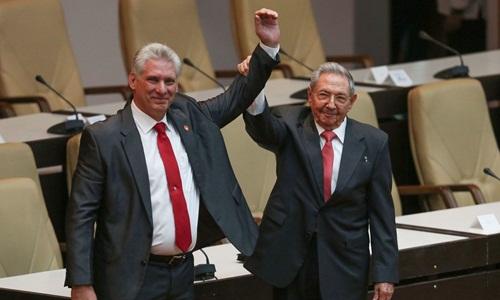 Ông Raul Castro (phải) nắm tayông Miguel Diaz-Canel sau khi ông này được bầu làm Chủ tịch Cuba. Ảnh: AFP.
