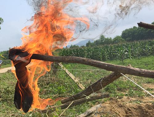 Nhúng vải vào dầu múc lên từ dưới hố, đem đốt cháy ngùn ngụt. Ảnh: Đức Hùng