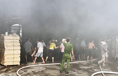Khói lửa bao trùm xưởng gỗ, nhiều công nhân tháo chạy ra ngoài, cố gắng dập tắt đám cháy nhưng bất thành. Ảnh: Nguyệt Triều