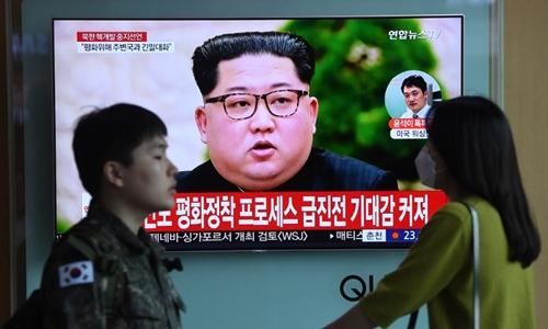 Người Hàn Quốc ở Seoul đi qua một màn hình chiếu tin tức về lãnh đạo Triều Tiên Kim Jong-un ngày 21/4. Ảnh: AFP.