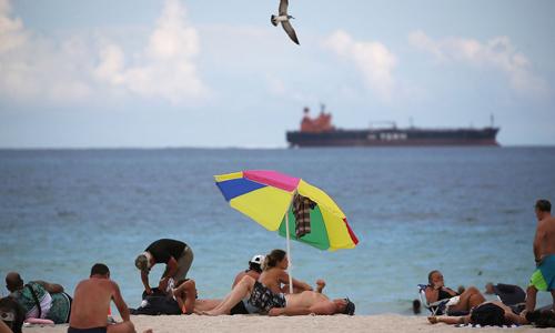 Khách du lịch phơi nắng trên bãi biển ở bang