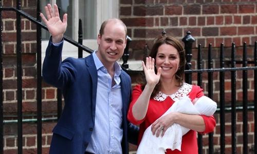 Vợ chồng hoàng tử William bế con trai mới sinh ra ngoài bệnh viện để chào công chúng ngày 23/4. Ảnh: AFP.
