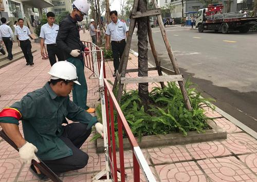 Lực lượng chức năng phá dỡ rào chắn bằng sắtdựng trên vỉa hè chung cư Vinaconex 7. Ảnh: Gia Chính.