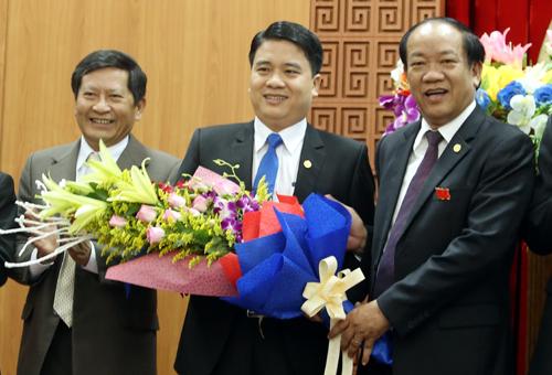 Ông Trần Văn Tân (giữa) nhận hoa chúc mừng từ Chủ tịch tỉnh Quảng NamĐinh Văn Thu. Ảnh:Đắc Thành.