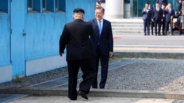 Lãnh đạo Triều Tiên Kim Jong-un và Tổng thống Hàn Quốc Moon Jae-in bắt tay tại đường ranh giới chia cắt hai miền. Ảnh: CNN.