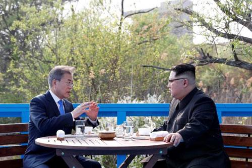 Tổng thống Hàn Quốc Moon Jae-in trao đổi với lãnh đạo Triều Tiên Kim Jong-un tại khu phi quân sự. Ảnh: AP.